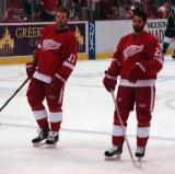 Dan Cleary and Mathieu Schneider stand at the blue line during pregame warmups.