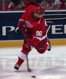 Tomas Holmstrom leans into a shot during pregame warmups.