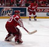 Chris Osgood knocks the puck aside as Henrik Zetterberg looks on during pregame warmups.