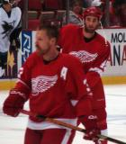 Kyle Quincey watches his teammates during pregame warmups as Kris Draper passes in front of him.
