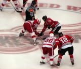 Henrik Zetterberg takes a center-ice faceoff against former Red Wing Robert Lang, with Tomas Holmstrom on his right wing.