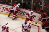 Nicklas Lidstrom and Jiri Hudler fight former Red Wing Robert Lang for the puck behind Dominik Hasek's net as Brian Rafalski looks on.