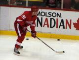 Johan Franzen practices with a puck along the boards during pre-game warmups.