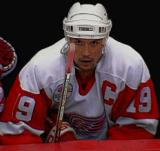 Steve Yzerman sits at the bench, looking up at the scoreboard.