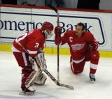 Chris Osgood and Nicklas Lidstrom talk in the neutral zone during pre-game warmups.