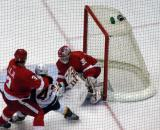 Dominik Hasek makes a save while Andreas Lilja holds up Alexander Radulov on his way to the net.