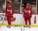 Dan Cleary and Henrik Zetterberg stand along the boards during practice.