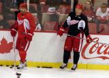 Henrik Zetterberg and Nicklas Lidstrom stand along the boards during practice.