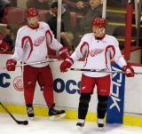Kirk Maltby and Derek Meech stand along the boards during practice.