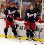 Andreas Lilja and Niklas Kronwall stand along the boards during practice.