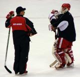 Chris Osgood talks with assistant coach Paul MacLean during practice.