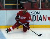 Andreas Lilja stretches along the boards during pre-game warmups.