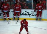 Andreas Lilja, Brian Rafalski, and Darren McCarty stand along the boards in the corner while Pavel Datsyuk skates through the faceoff circle.