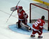Chris Osgood stretches out to try to stop a shot as Tomas Holmstrom skates past during pre-game warmups.