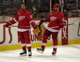 Dallas Drake and Brett Lebda stand along the boards during pre-game warmups.