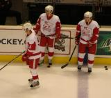 Jakub Kindl, Evan McGrath and Logan Pyett stand along the boards during pre-game warmups before a Grand Rapids Griffins game.