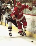 Vyacheslav Kozlov tries to break away from a Washington Capital while carrying the puck along the boards.