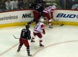 Henrik Zetterberg battles Blue Jacket Jiri Novotny in the corner, with Dan Cleary providing support and Columbus' Christian Backman watching it all.