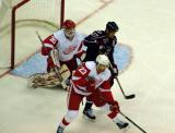 Brad Stuart attempts to clear the puck away from Chris Osgood's crease, with Manny Malhotra of the Columbus Blue Jackets looking for a tip-in.