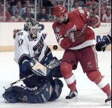 Tomas Holmstrom crashes into Washington goalie Olaf Kolzig as the puck bounces between them.