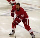 Kris Draper picks up a puck in the neutral zone during pre-game warmups.