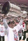 Scotty Bowman wears a rare smile on his face as he lifts the Stanley Cup after the 1998 Finals.