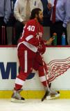Henrik Zetterberg leans against the boards at the bench during pre-game warmups.