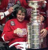 Vladimir Konstantinov holds the Stanley Cup while being surrounded by the Red Wings.