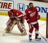 Chris Osgood stays out of his crease as Kris Draper clears pucks from the net during pre-game warmups.