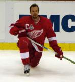 Nicklas Lidstrom crouches along the boards during pre-game warmups.