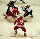 Justin Abdelkader takes a draw against Buffalo's Paul Gaustad during a preseason game, with Patrick Eaves on his wing.