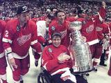 Vladimir Konstantinov carries the Stanley Cup while being pushed around the ice by fellow Russians Viacheslav Fetisov and Igor Larionov.