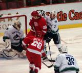 Brian Rafalski fires a shot on Vancouver's Roberto Luongo with Drew Miller screening, while former Red Wing Mathieu Schneider and Jannik Hansen defend.