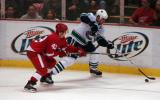 Darren Helm pursues Vancouver's Willie Mitchell along the boards.
