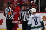 Brad May yaps at Vancouver's Willie Mitchell while the two are separated by officials.