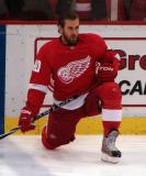 Henrik Zetterberg kneels near the blue line during pre-game warmups.