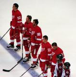 Jonathan Ericsson, Danny Cleary, Mike Modano, Tomas Tatar, and Ruslan Salei stand with two youth hockey players for the singing of The Star-Spangled Banner before a preseason game.