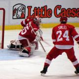 Jimmy Howard knocks aside a shot while Ruslan Salei skates in to clear a possible rebound.