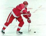 Ulf Samuelsson makes an outles pass while cutting between the circles in the Red Wings zone.