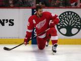 Henrik Zetterberg stretches along the boards during pre-game warmups.