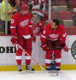 Johan Franzen and Todd Bertuzzi talk while standing along the boards during pre-game warmups before a preseason game.