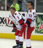 Logan Pyett and Doug Janik stand near the boards during pre-game warmups before a Grand Rapids Griffins game.
