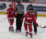 Henrik Zetterberg talks with linesman Mike Cvik and Niklas Kronwall skates away from referee Don Van Massenhoven after a conversation during a stoppage in play.