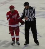 Henrik Zetterberg talks with linesman Mike Cvik during a stoppage in play.