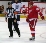 Johan Franzen talks with referee Gord Dwyer during a stoppage in play.
