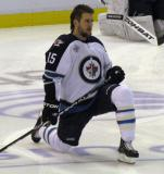 Winnipeg's Tanner Glass stretches near center ice during pre-game warmups.
