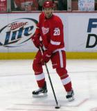 Drew Miller carries a puck through the right faceoff circle during pre-game warmups.