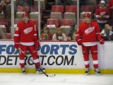 Drew Miller and Justin Abdelkader stand along the boards during pre-game warmups.