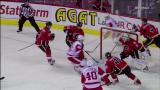 Valtteri Filppula feeds Jiri Hudler from behind the Calgary net for a shot past goalie Miikka Kiprusoff.