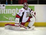 Jordan Pearce stretches along the boards during pre-game warmups before a Grand Rapids Griffins game.
